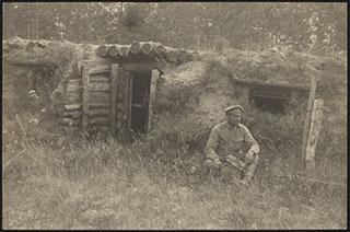 Фотография военного около землянки